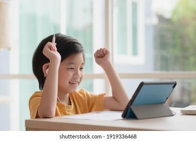 Cute Asian Child Learning Class lernt online mit Videoanruf von Tablet zu Hause.Soziales Distanzkonzept