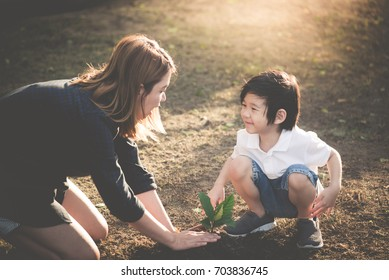Cute Asian child and mother planting young tree on the black soil