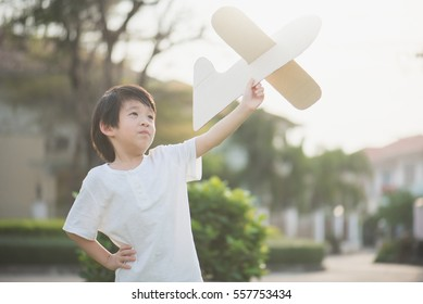 Cute Asian child playing cardboard airplane in thee park outdoors