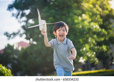 Cute Asian child playing cardboard airplane in the park outdoors