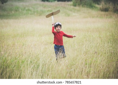 Cute Asian child playing cardboard airplane in the grass field
