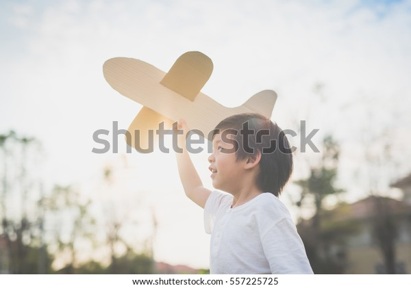 Cute asiatisches Kind, das im Park im Freien Pappflugzeug spielt