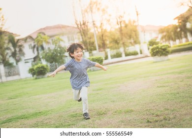 Cute Asian child playing pilot aviator in thee park outdoors