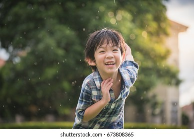 Cute Asian child playing pilot aviator in the park under the rain