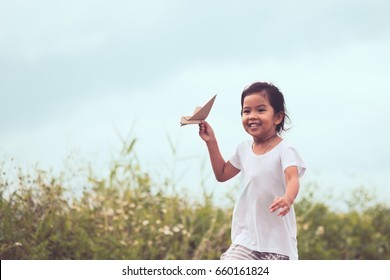 Cute asian child playing toy paper airplane in the meadow in vintage color tone