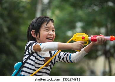 Cute Asian child playing with water gun in the summer