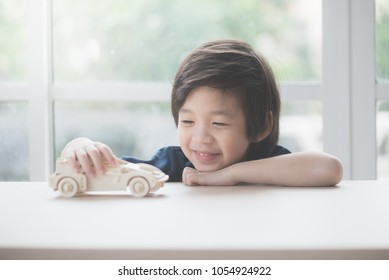 Cute Asian child playing wooden toy car on a table