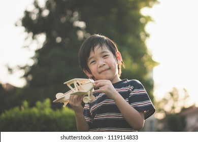 Cute Asian child playing wooden toy plane in the park