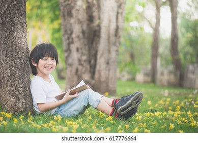 Cute Asian child reading a book under the tree