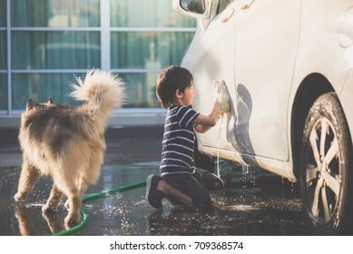 Cute asian child washing a car on summer day