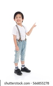Cute Asian child  in white t-shirt and jeans pointing on white background isolated