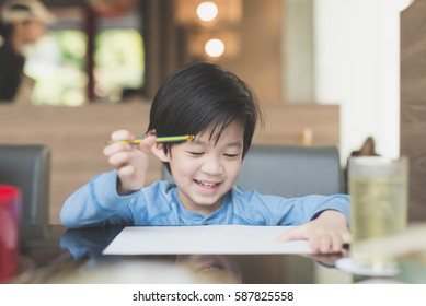 Cute Asian child writing on white paper