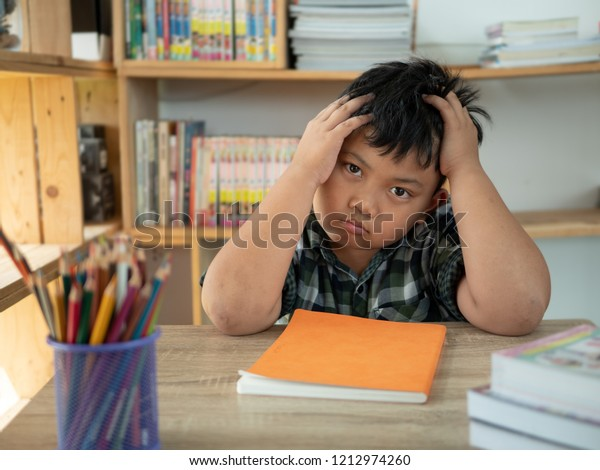 Cute asian children is bored and tired with doing homework on desk in the room. education concept