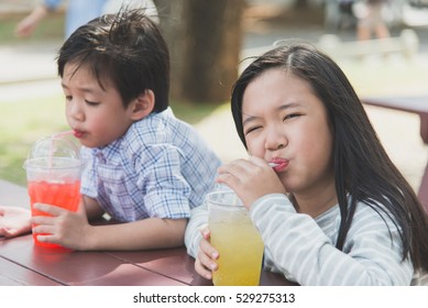 Cute asian children drinking fresh  juice in the park outdoor