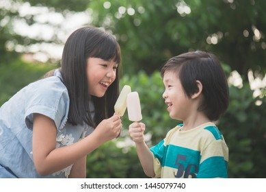 Cute Asian children eating an japanese ice cream outdoors