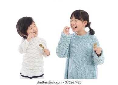 Cute asian children eating japanese dessert on white background,isolated