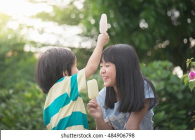 Cute Asian children eating  japanese ice cream outdoors