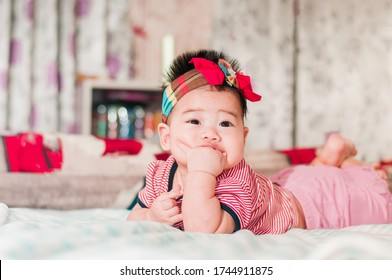 Cute Asian children are happily sucking their hands in the bed ,The concept of a cute and healthy child with happiness.