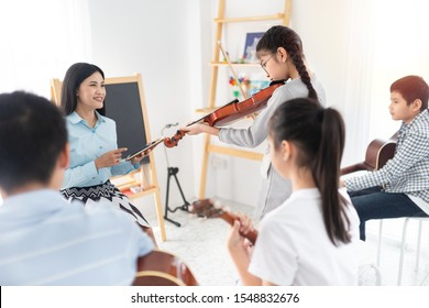 cute asian children holding violin on her shoulder and play violin, she show violin skill and present melody and song to teacher and friends, asian children group in musical training time