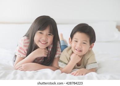 Cute asian children lying on white bed