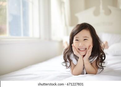 Cute asian children lying on white bed.