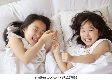 Cute asian children lying on bed.