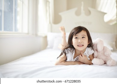 Cute asian children lying on white bed.