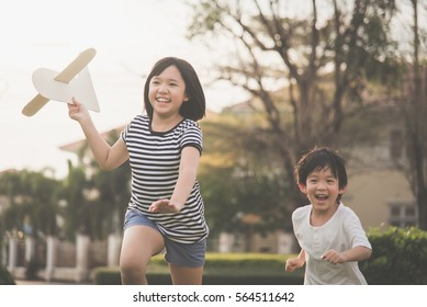 Cute Asian children playing cardboard airplane together in the park outdoors
