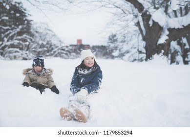 Cute Asian children playing on snow in the park together , Aomori Japan