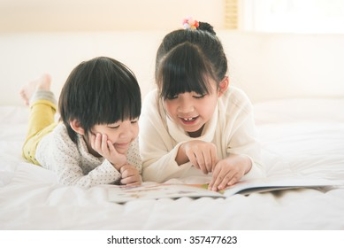 Cute asian children reading book on white bed,vintage filter