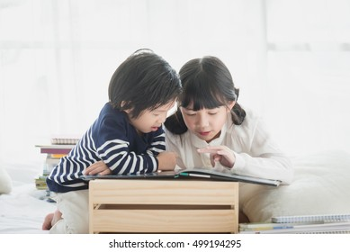 Cute asian children reading a book on white bed