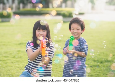Cute Asian children Shooting Bubbles from Bubble Gun in the park