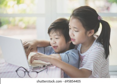 Cute Asian children using tablet together
