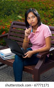 Cute Asian college student thinking with laptop and pen pressed against her mouth sitting outside on a university campus bench.  20s female Asian Thai model of Chinese descent looking away