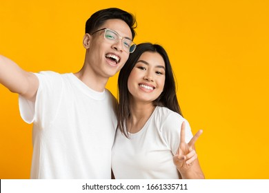 Cute asian couple in love taking selfie over yellow studio background, copy space