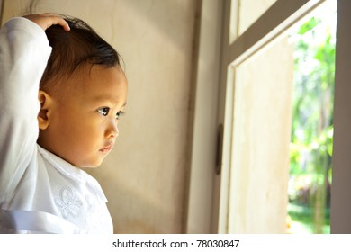 cute asian ethnic little girl dressed in white look out the window
