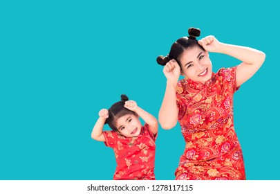 cute Asian family with cheongsam Qipoa Chinese Traditional dress costume in cute and smile action on red isolated background in China New year festival. (include clipping path)