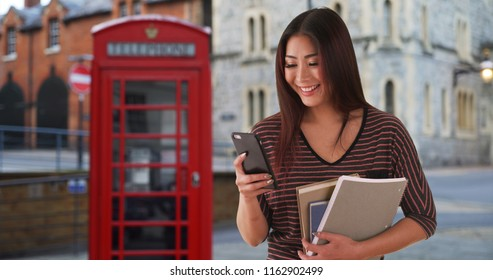 Cute Asian female studying in England laughs at funny text from boyfriend