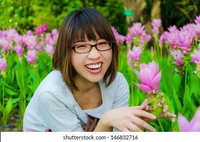 Cute Asian female Thai girl is very happy with flowers Siam Tulip flora field in final retouch  She is laughing with joy which show a strong mental health expression.
