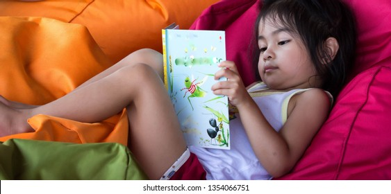 cute asian female toddler child while reading a book and sitting on a bean bag in a beach resort in asia