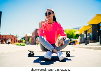 Cute Asian female in trendy sunglasses and streetwear resting at longboard and dreaming about skater career, happy hipster girl in sweatshirt enjoying free time for practicing boarding in city