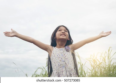 Cute Asian Girl attractive raised hand Freedom at beauty nature field and kid happy