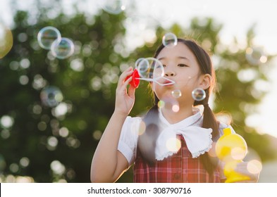 Cute asian girl is blowing a soap bubbles, Outdoor Portrait