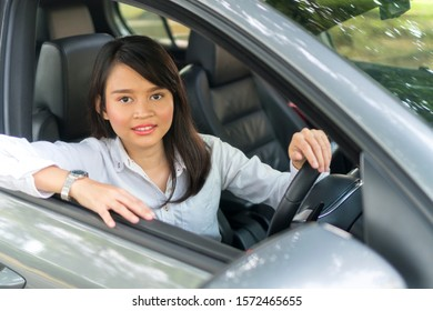 Cute Asian girl in the car smiling e-hailing concept