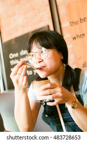 Cute asian girl drinking latte art coffee at cafe in the city.