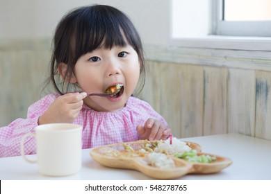cute asian girl eating lunch at kindergarten.