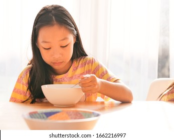 Cute Asian girl eats rice soup for breakfast together near window at home.