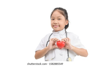 cute asian girl future doctor dressed white medical apron with stethoscope and show red heart in hand isolated on white background, Health care and love concept