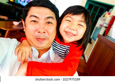 cute Asian girl hugging her father or uncle, family theme
