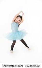 Cute Asian girl in light blue dress performing ballet with smiling face, isolated on white background.